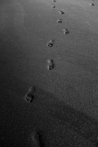 grayscale-photo-of-footprints-on-sand-3646206